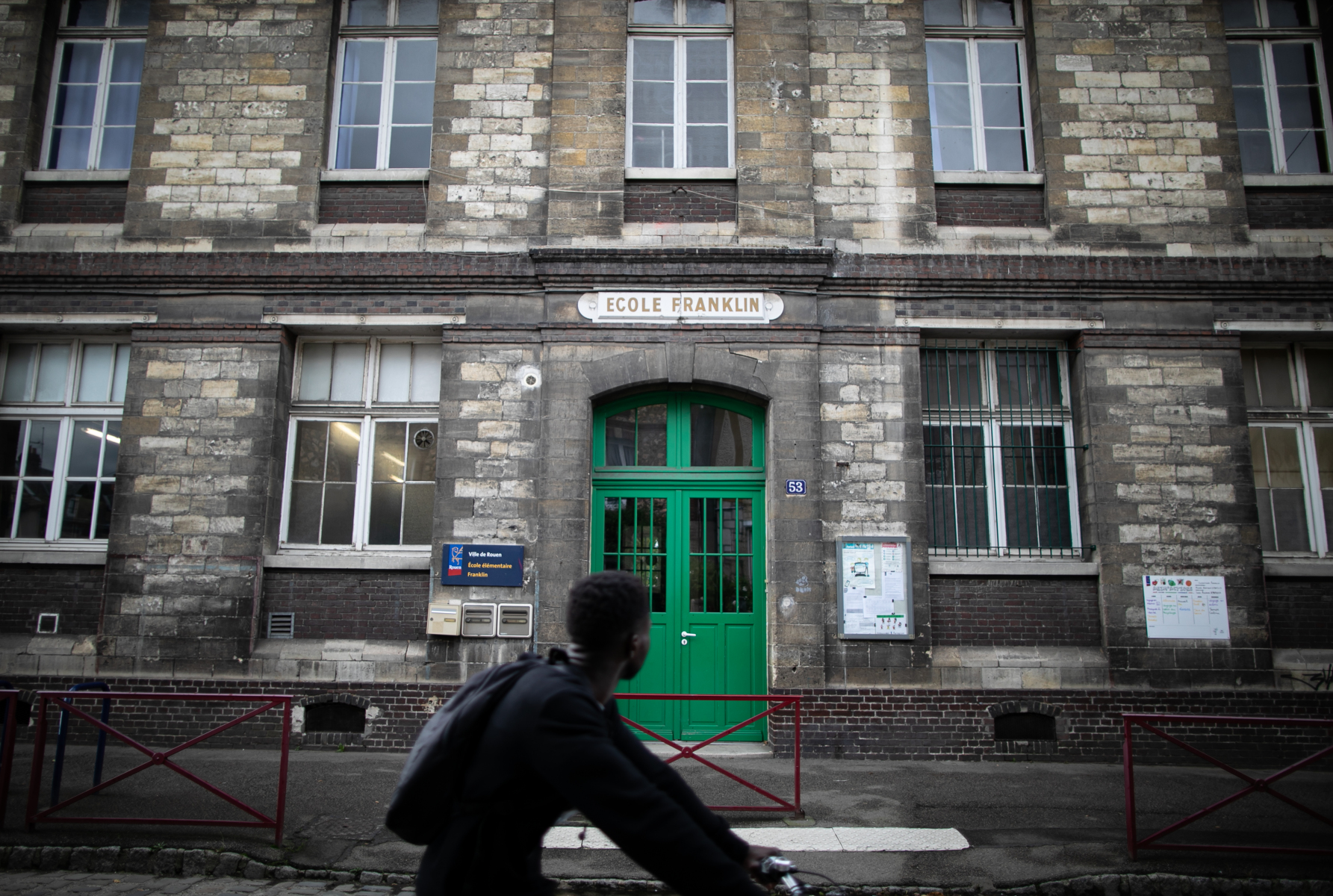 A child  rides past the Franklin school on October 1, 2019, in Rouen, northern France. Some schools advide parents th get back children home, on october 1, 2019. Schools were shuttered for two days and reopened on September 30, 2019. The huge blaze erupted on September 26 in a storage facility owned by Lubrizol, a manufacturer of industrial lubricants and fuel additives.