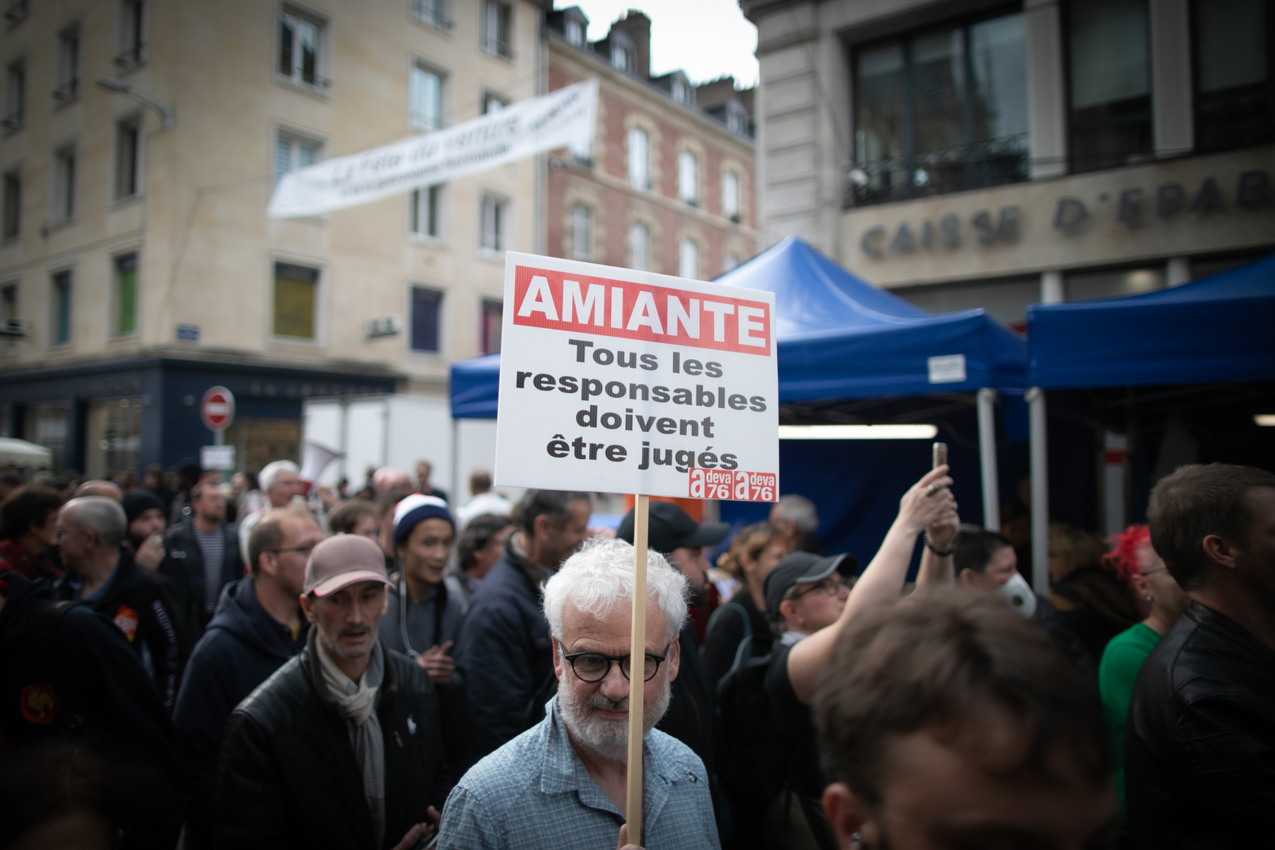 "A militant holds a banner reading ""All responsives mus be judged"" during a demonstration on october 12, 2019, in Rouen, Normandy, to protest after the fire at the Lubrizol factory which occures on september 26, 2019."