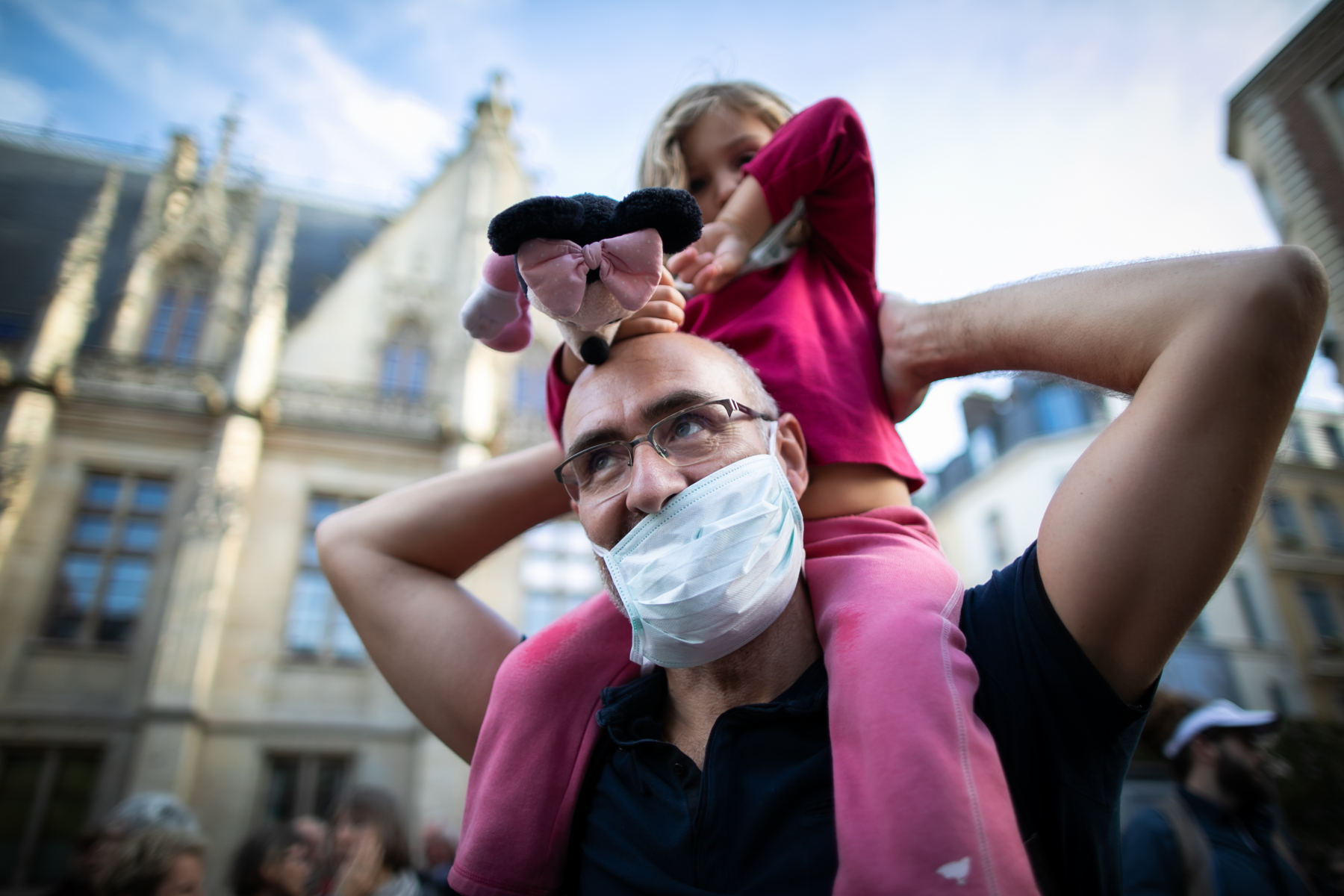 A man wears a mask as he holds her daughter during a demonstration challenging the management of the lubrizol case, on October 26, 2019, in Rouen, one month after the fire at the Lubrizol factory.